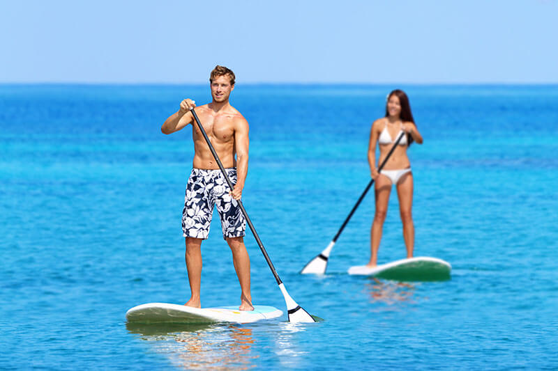 a man and woman paddleboarding